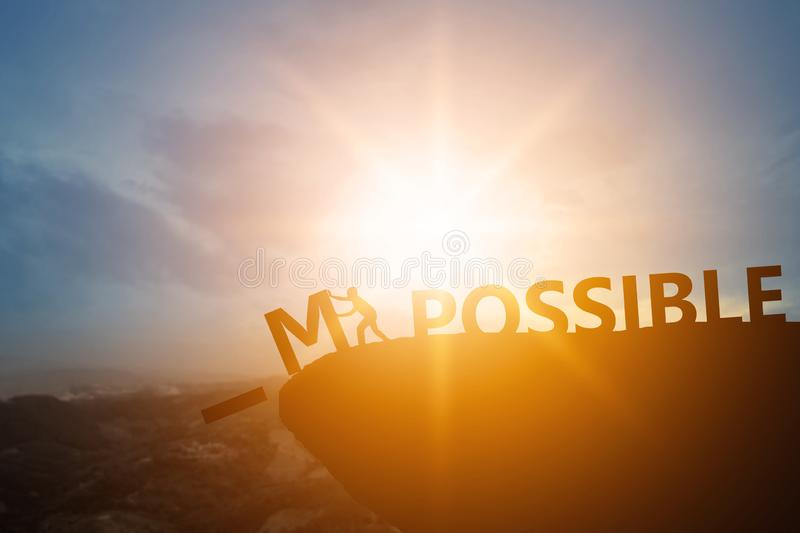Silhouette of people success and chance impossible to possible text on cliff in sunset , can and development concept stock photo