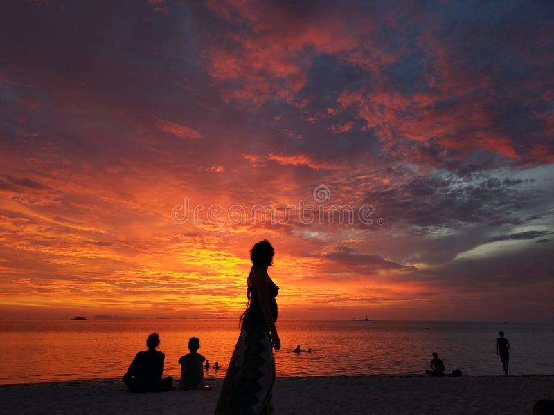 Silhouette of people on sunset beach. Side view of female silhouette on tropical coastline against multicolored tropical sunset stock photography