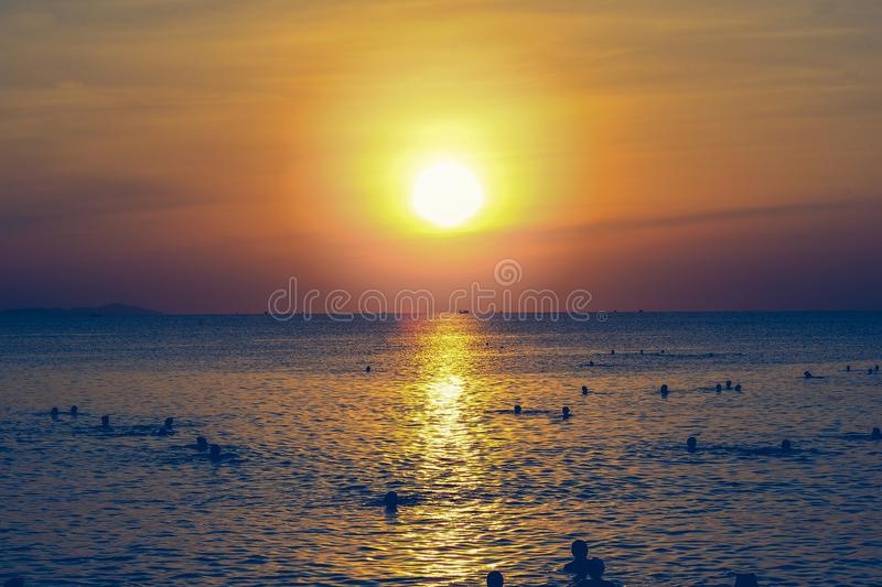 Silhouette of People Swimming in the Ocean During Sunset stock photography