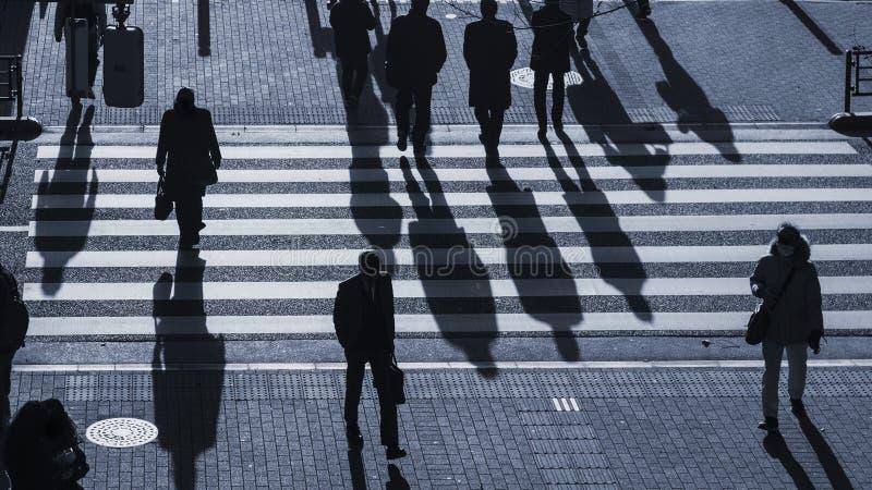 Silhouette people walk on pedestrian crosswalk at the junction. The silhouette people walk on pedestrian crosswalk at the junction street with the dark shadow of royalty free stock photography
