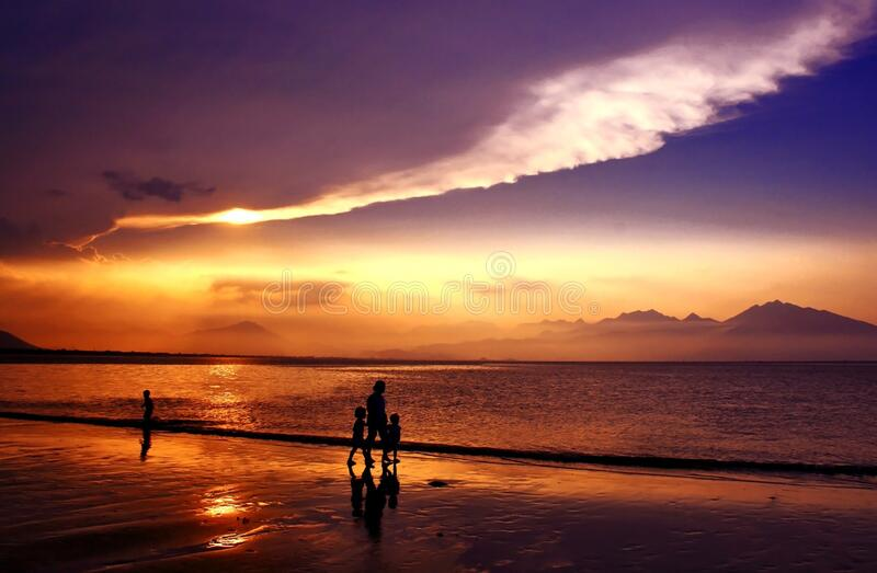 Silhouette of People Walking on Seashore Under Gray and White Clouds during Daytime stock photo