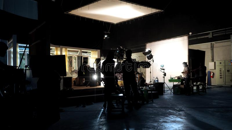 Silhouette of people working in big production studio. For shooting or recording movie video by digital camera and lighting set royalty free stock images
