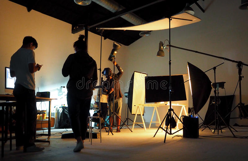 Silhouette of people working in production studio. Silhouette of people working in production studio for shooting or recording by digital camera and lighting royalty free stock images