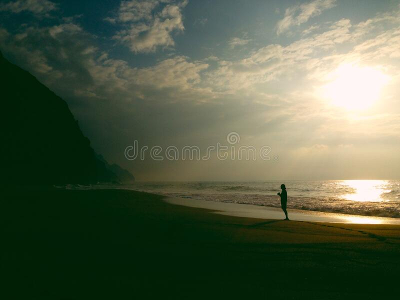 Silhouette of person on beach at sunset royalty free stock photos