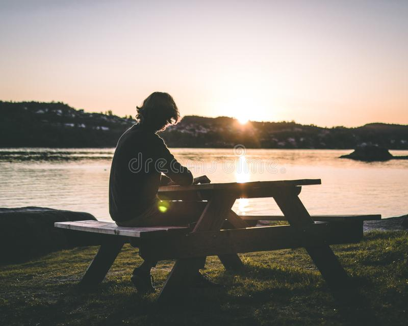 Silhouette of Person in Black Top Sitting on Picnic Bench Near Body of Water during Sunset stock photography