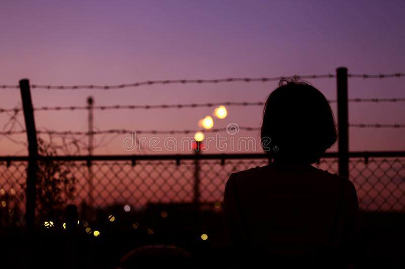 Silhouette of Person in Front of Fence royalty free stock images