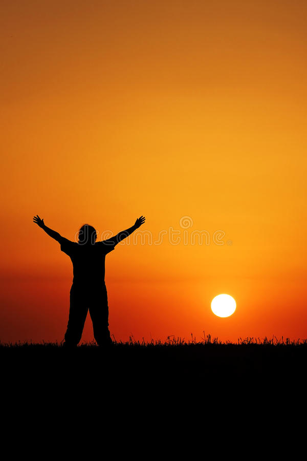 Silhouette of person greeting the sun stock images