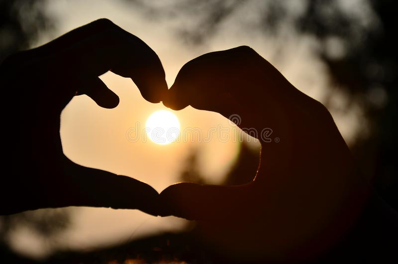 Silhouette of Person Hand Doing Heart Shape during Sunset stock photos