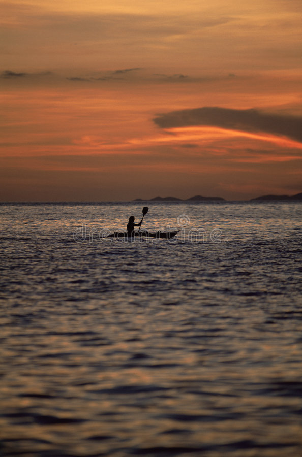 Silhouette of person kayaking at sea during sunset royalty free stock image