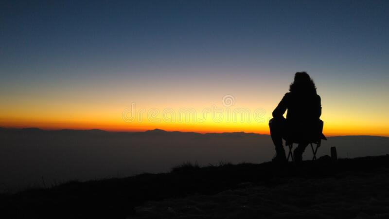 Silhouette of person on mountain at sunset stock photos