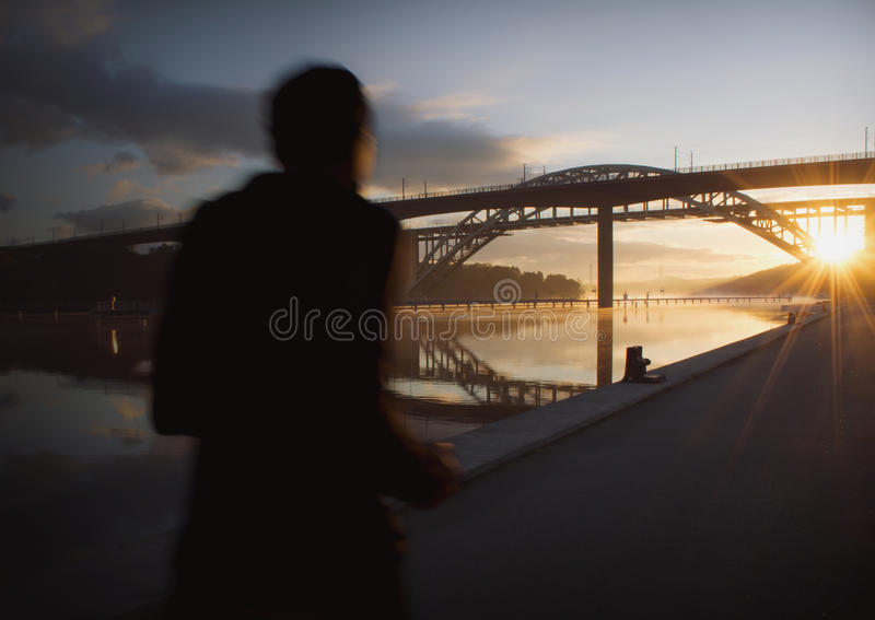 Silhouette of a person running at beautiful, early dawn under a bridge. Silhouette of a person running fast an early morning, sun just rising. Urban landscape royalty free stock image