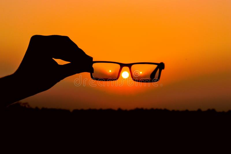 Silhouette of Person's Hand Holding Eyeglasses during Golden Hour royalty free stock images