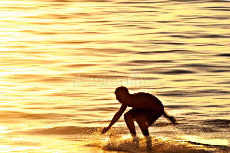 Silhouette of a person skimboarding at sunset. Silhouette of a person skimboarding in the golden yellow light of sunset royalty free stock images