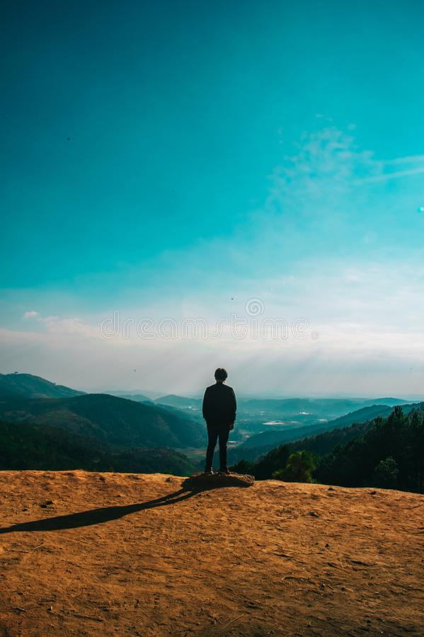 Silhouette of Person Standing on Hill Under Clear Blue Sky stock images