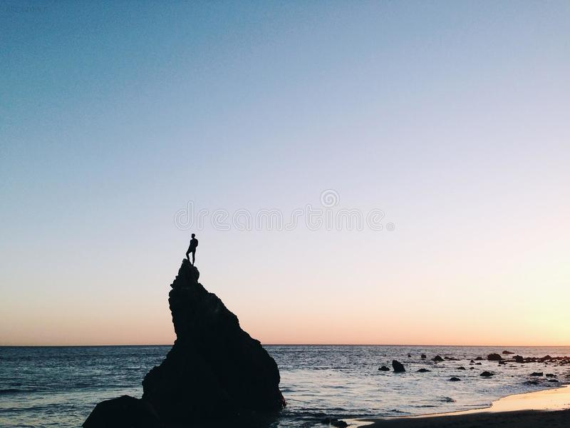 Silhouette of Person Standing on Rock on Beach Shore during Yellow Sunset stock images