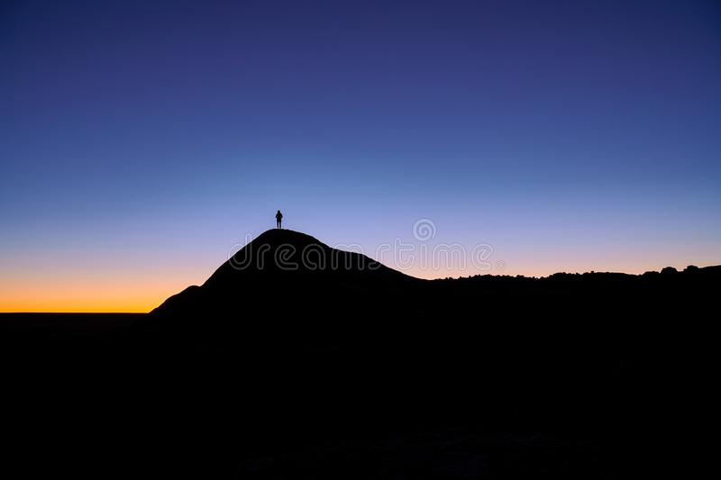Silhouette of a person standing at the rock in the distance stock images