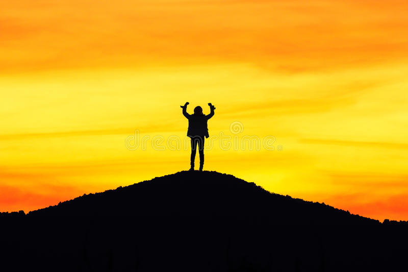 Silhouette of the person on sun set background,successful arm up. Man is on top of hill celebrating success with sunrise stock image