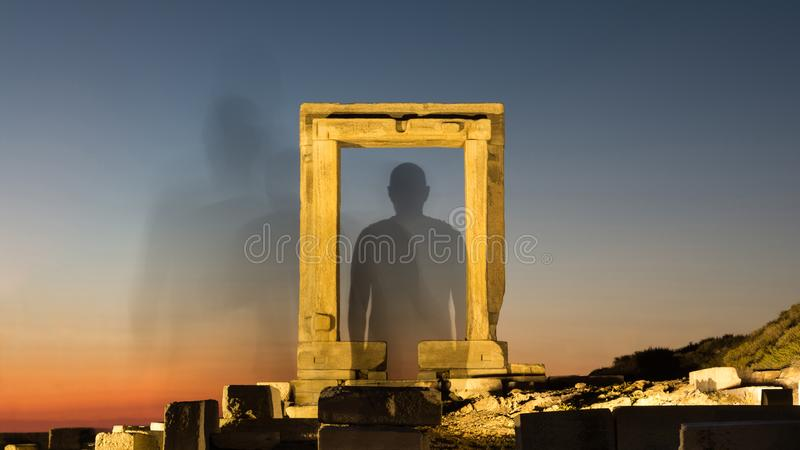Silhouette of a person vanish through a illuminated ancient gate to space.  royalty free stock images