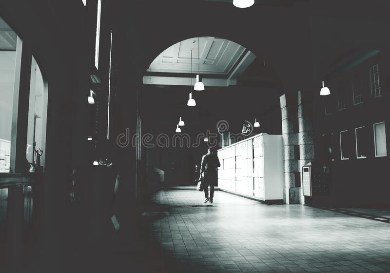Silhouette of a Person Walking on a Grey Floor Tiles Beside White Cabinet in Dark Room stock images