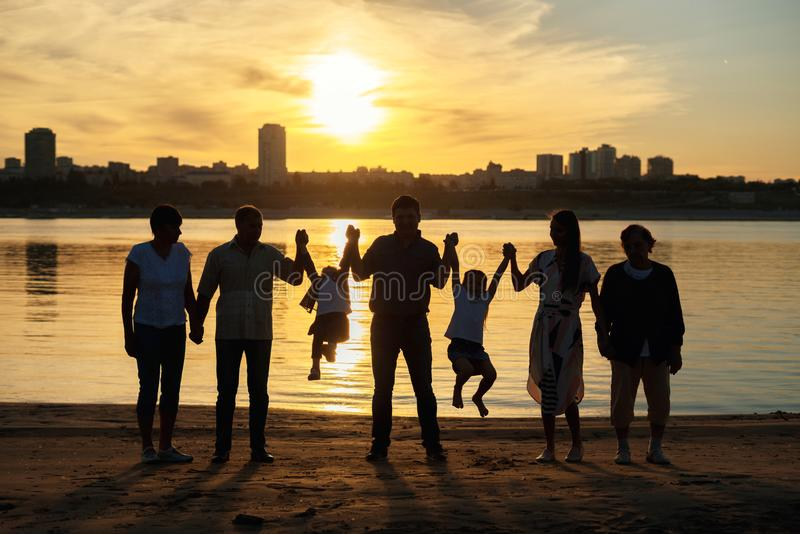 The silhouette photo of big family with the grandmother and small children on walk on the river bank in the sunset sun. Concept of united family and different stock photo