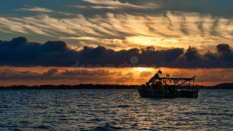 Silhouette Photo of Boat on Ocean during Golden Hour royalty free stock photography