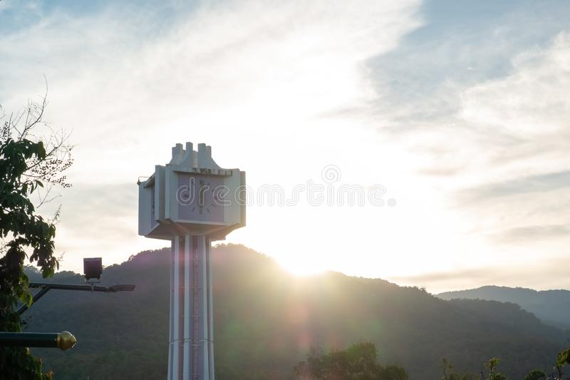 Silhouette photo of clock tower. With mountain view and sun flare behind as background stock photos