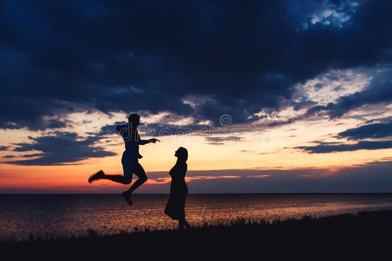 Silhouette photo of a couple in love on the background of a beautiful sunset sky and the sea. The guy jumped high. stock photography
