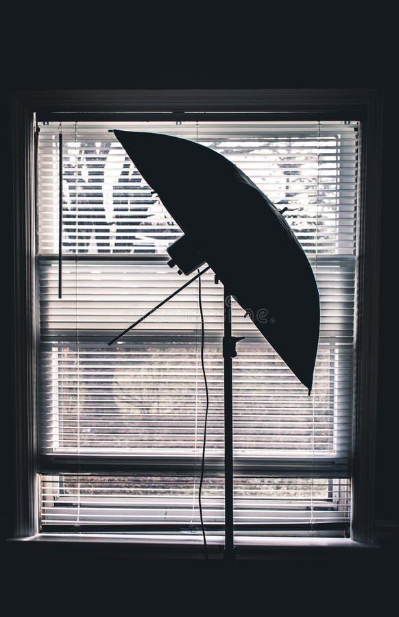 Silhouette Photo Du Studio Umbrella Près Des Aveugles De La Fenêtre Blanche Dans La Salle photo stock