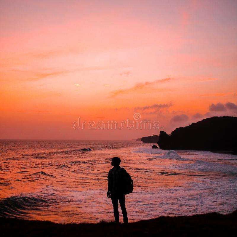 Silhouette Photo of Man With Backpack Standing in Seashore during Golden Hour royalty free stock image