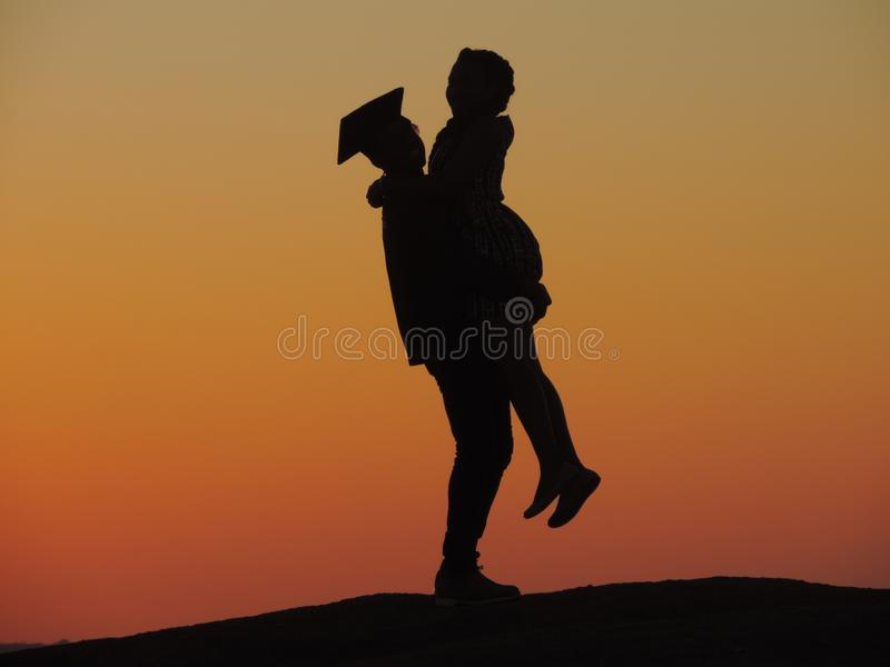 Silhouette Photo Of Man Carrying Woman Under Orange Sky royalty free stock photo
