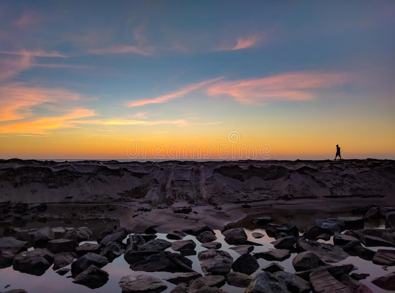 Silhouette Photo of Man Walking on Hill Near Body of Water and Rock Formations royalty free stock photography