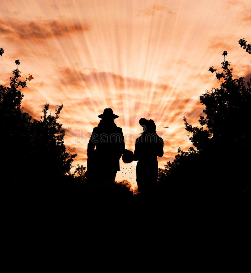 Silhouette Photo of Man and Woman Wearing Hat Standing Between Trees during Golden Hour royalty free stock photography
