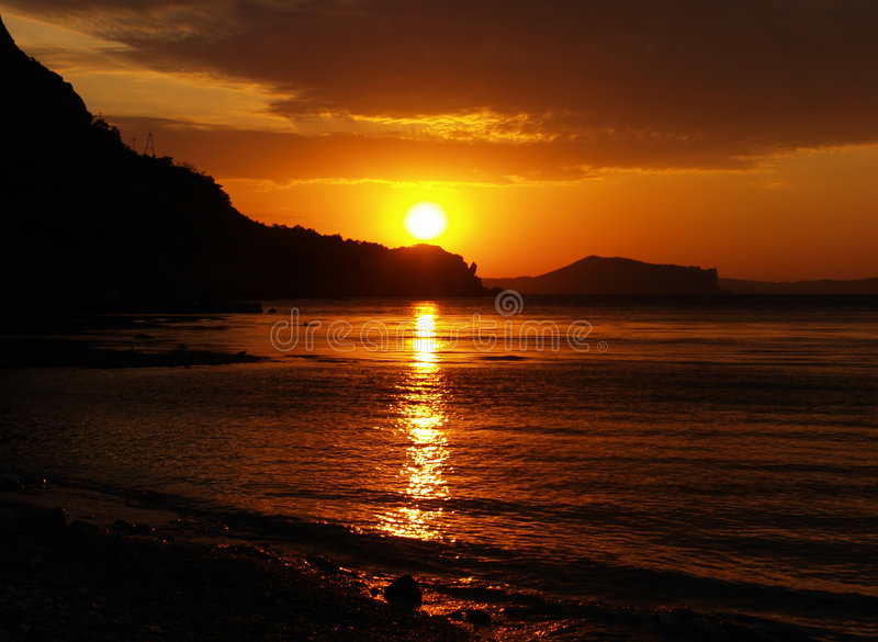 Silhouette photo, mountain sea. Sun, clouds,sky. beautiful red and orange colors royalty free stock images