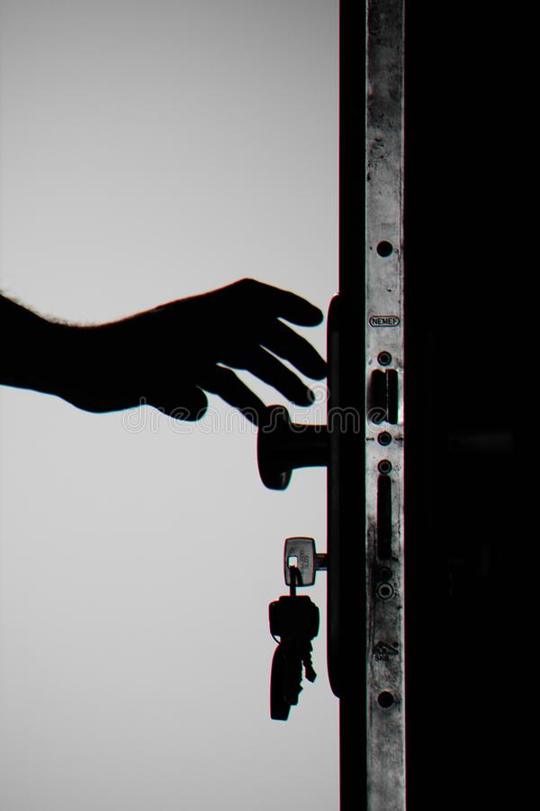 Silhouette Photo of Person Holding Door Knob royalty free stock photo
