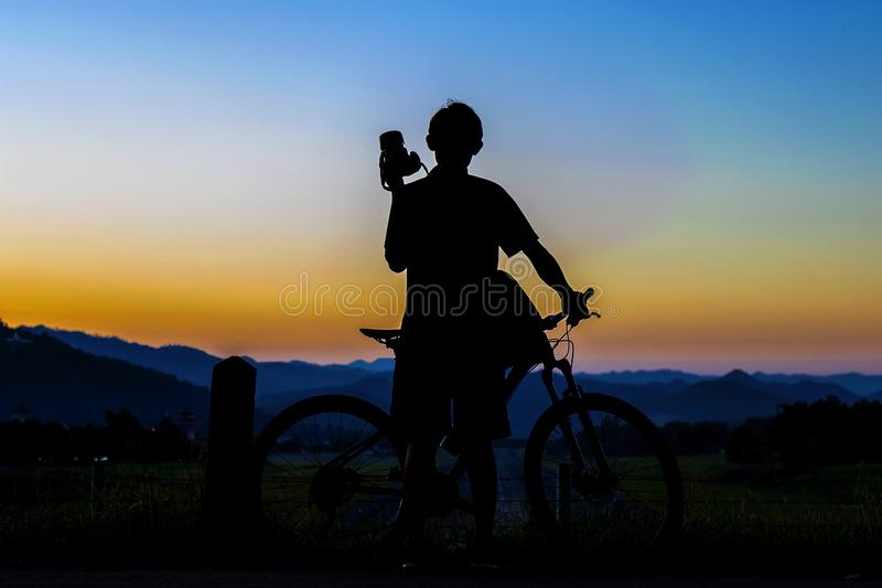 Silhouette of photographer in action take photo with bike on mountain with sunrise. stock photos