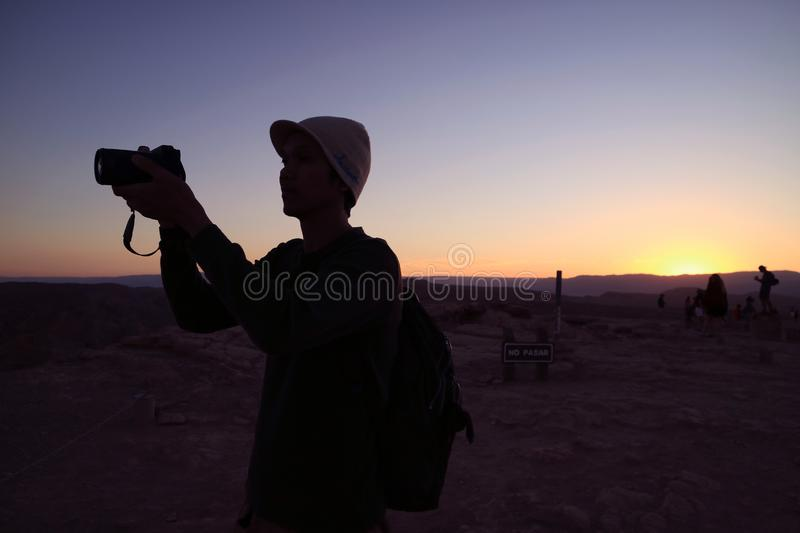 Silhouette of a photographer against sunset sky, the notice board NO PASAR behind means No Passing. Beauty in nature stock photography