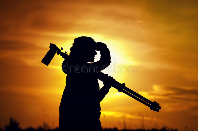 Silhouette of photographer with camera and tripod royalty free stock images