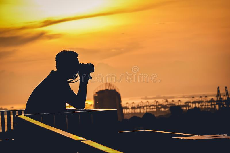 Silhouette of a photographer like to travel and photography, taking pictures of the beautiful city life sunset ,sunrise. Silhouette of a photographer like to royalty free stock photo