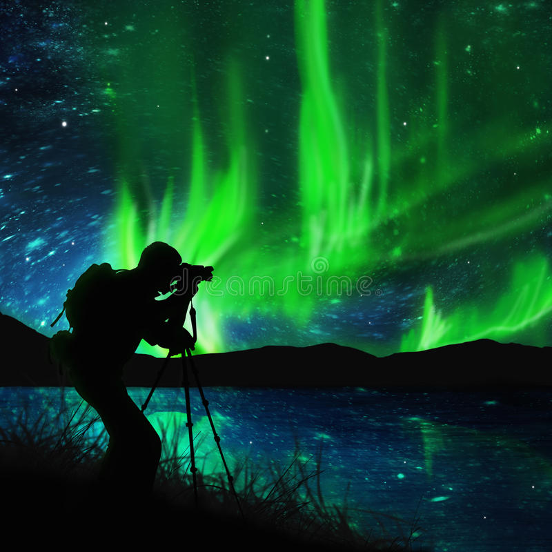 Silhouette of photographer shooting aurora royalty free stock photography