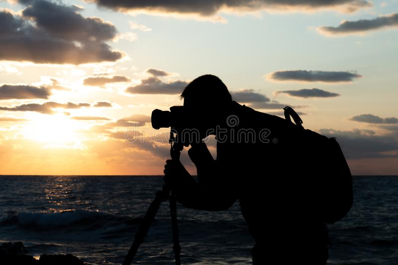 Silhouette the photographer shooting a colorful sea sunset. The rocky shore is washed by sea waves. Photographer concept stock image