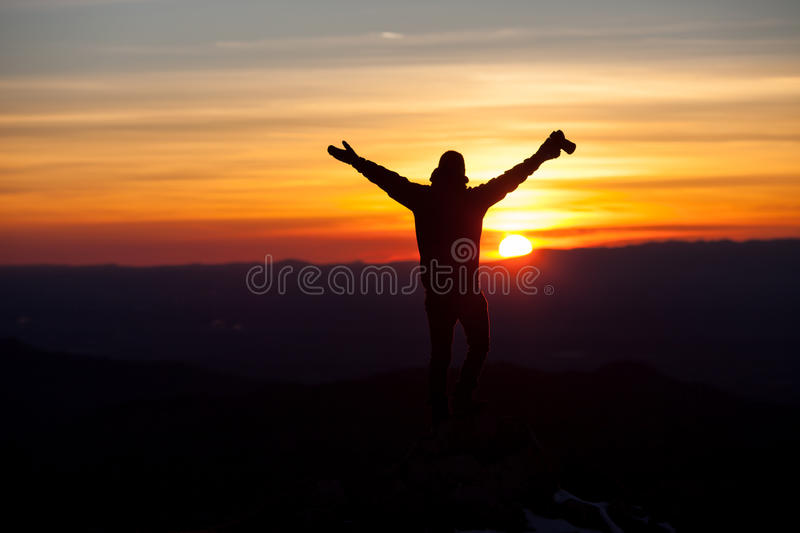 Silhouette of photographer in sunset. Spreading arms royalty free stock photos