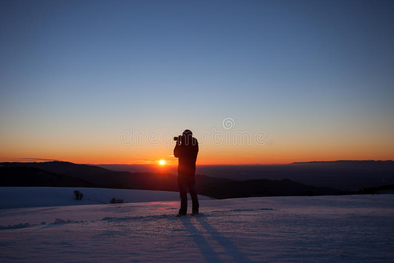 Silhouette of photographer in sunset. In winter landscape royalty free stock image