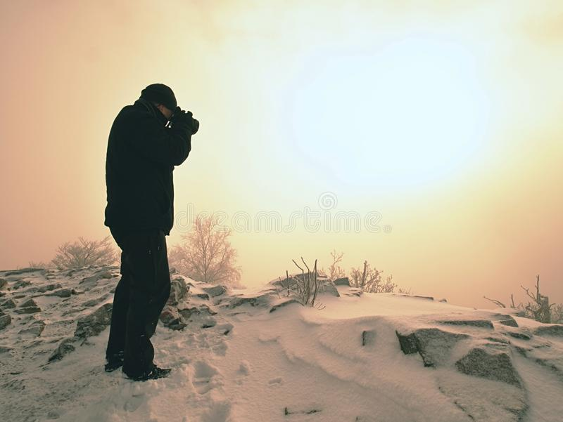 Man photographing magic misty landscape in winter the mountains. royalty free stock photos