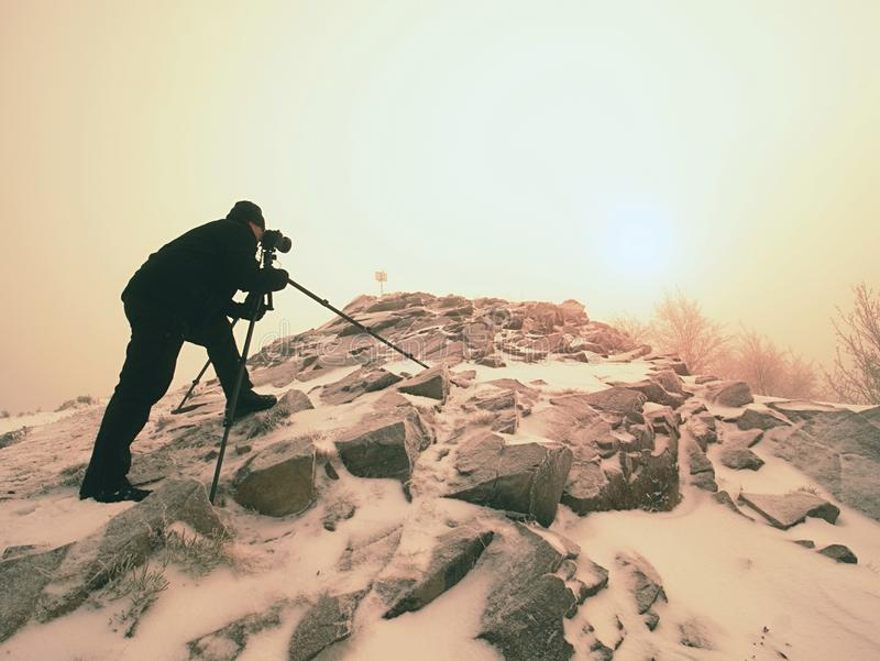 Man photographing magic misty landscape in winter the mountains. royalty free stock image