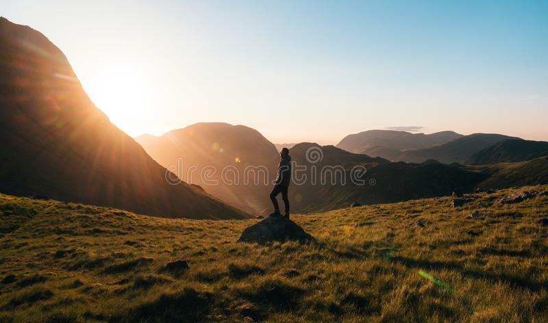 Silhouette Photography of Person Standing on Green Grass in Front of Mountains during Golden Hour stock photo
