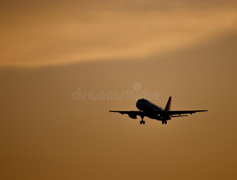 Silhouette of a plane landing at sunset, plane against colored sky stock images