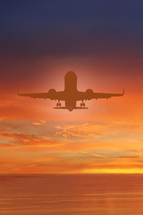 Silhouette of plane in the sky above Sea at Sunset. travel, flight, vacation Concept. Low key photo. relax time stock photo
