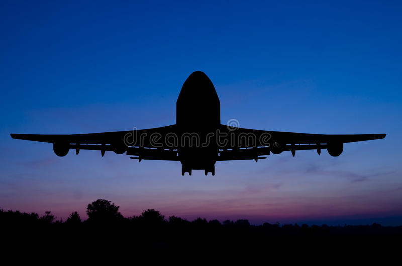 Silhouette of the plane on a sunset background. royalty free stock images