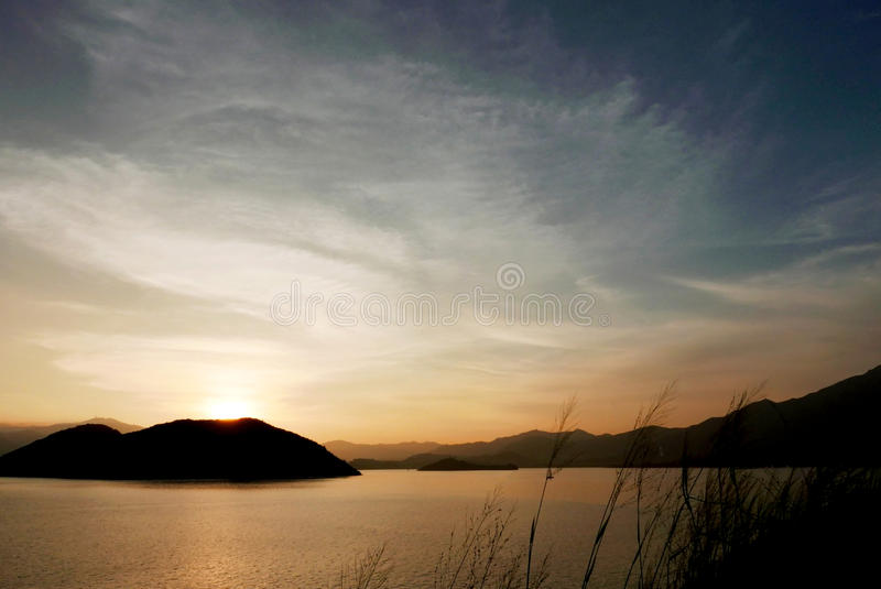 The silhouette of plants and mountain with gradient sunset. The silhouette of plants and mountain with the gradient sunset stock photography