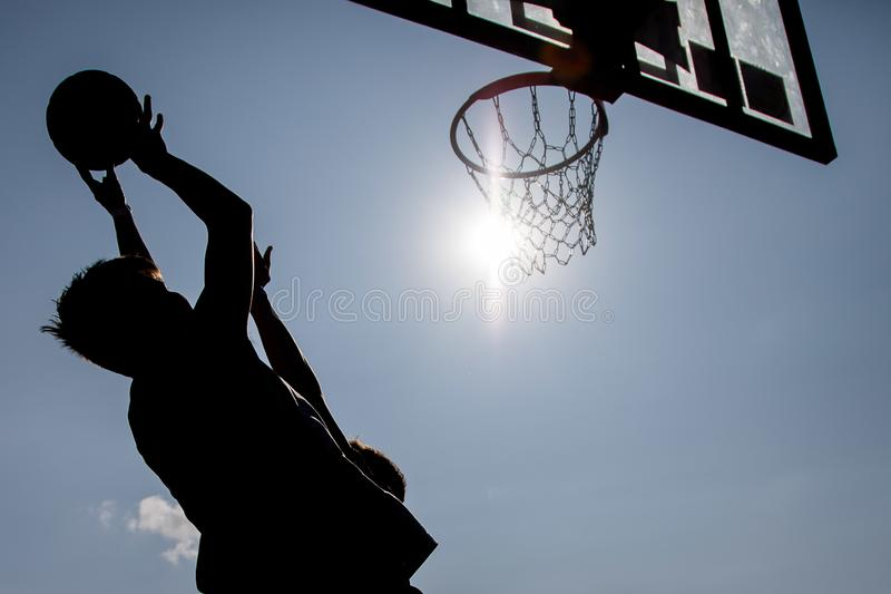 Silhouette play basketball young boys stock images
